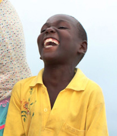 Young Haitian boy throws his head back in laughter. Resilience Through Laughter.