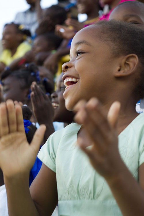 A laughing child claps as she watches the performance. Donate.