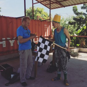 plain clothes clowns rehearse with a black and white checkered race flag and cone-shaped yellow hat