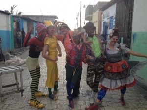 Group of local clown and Clowns Without Borders artists pose for the picture in a stone paved alley in Cite Soleil