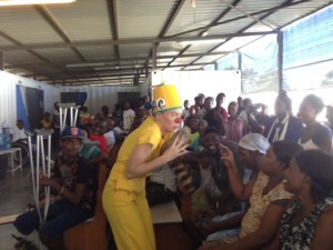 clown wearing all yellow entertains inside the free MSF clinic in Haiti where people wait to be treated for injuries and burns